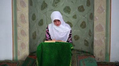 Young muslim girl reading Quran in mosque — Stock Video