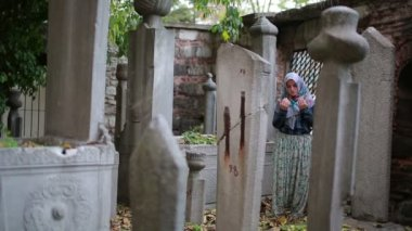 Muslim girl praying in small graveyard — Stock Video