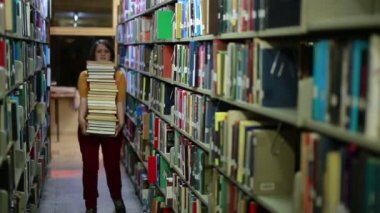 Distressed female student wandering between shelves — Stock Video