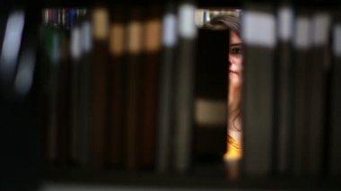 Female student wandering between shelves — Stock Video
