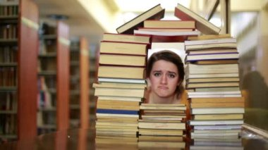 Sad female student gazing through house-shaped stack of books — Stock Video