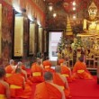 Buddhist monks pray in temple - Stock Photo