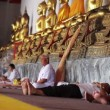 Sits under golden buddha statues — Stockvideo