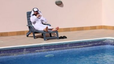 Saudi arabian man talking on phone at swimming pool — Stock Video