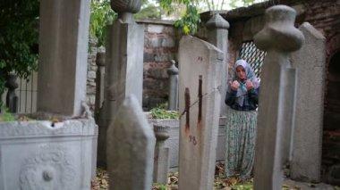 Muslim girl praying in small graveyard — Stock Video