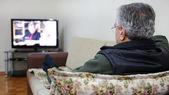 Senior man watching TV — Stock Photo
