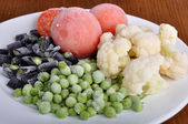 Frozen tomato, asparagus, peas and cauliflower on a plate — Stock Photo