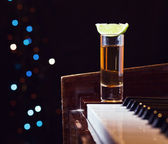 Glass with tequila on a piano — Stock Photo