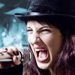 Girl with microphone in black top-hat — Stock Photo