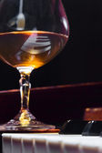Snifter with brandy on a piano — Stock Photo
