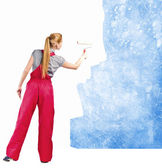 Woman in red overalls paints the soiled wall — Stock Photo