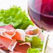 Glass with red wine and ham - Stock Photo
