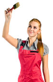 Young woman in red overalls with brush — Stock Photo