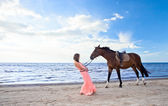 Girl with horse on seacoast — Stock Photo
