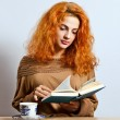 woman with book and tea cup — Stock Photo