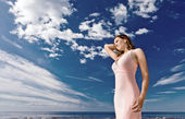Girl in pink dress on seacoast — Stock Photo