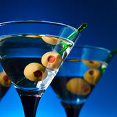 Glasses with martini and green olives — Stock Photo