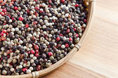 Peppercorns on wooden table — Stock Photo