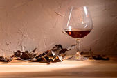 Brandy and dried oak leaves — Stock Photo