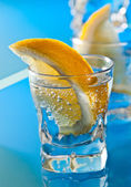 Gin with lemon on a glass table — Stock Photo