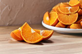 Cut tangerines on wooden table — Stock Photo