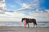 Beautiful girl with horse on seacoast — Stock Photo