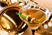 Saxophone and martini with green olives  — Stock Photo