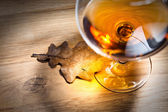 Brandy and dried oak leaf — Stock Photo
