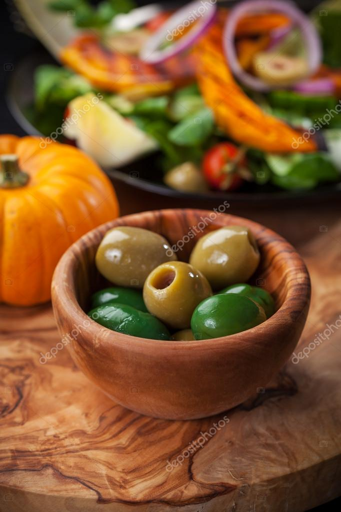 Delicious green olives in the bowl with salad — Stock Photo #13395425