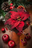 Christmas flower with decoration on wooden table — Stock Photo