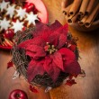 Christmas flower with decoration on wooden table - Stock Photo
