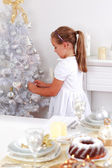 Cute girl decorating Christmas tree — Stock Photo