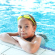 Happy girl with goggles in swimming pool - Stock Photo