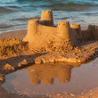 Sandcastle - concept of making save building — Stock Photo #27825039