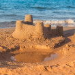 Sandcastle - concept of making save building — Stock Photo #27826383