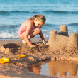 Child builds sandcastle on the beach — Stock Photo