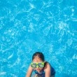 Happy girl with goggles in swimming pool — Stock Photo #50246059