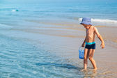 Boy looking for sea shells — Stock Photo