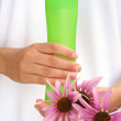 Hands of young woman holding cosmetics bottle and fresh coneflowers — Stock Photo #18172081
