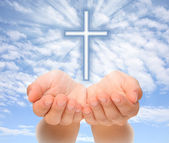 Hands holding Christian cross with light beams over sky — Stock Photo
