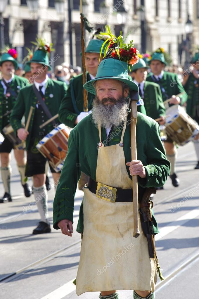 MUNICH, GERMANY - SEPTEMBER 23: an ancient tree feller and a music drum band in traditional bavarian clothes participates in the opening parade of Oktoberfest  Stock Photo #13293803