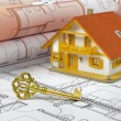 Resdential house and golden key over building plan — Stock Photo