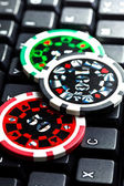 Poker chips on computer keyboard — Stock Photo