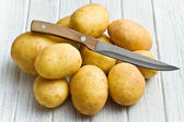 Raw potatoes with knife — Stock Photo
