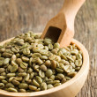 Green coffee beans in wooden bowl — стоковое фото #13641490