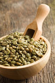 Green coffee beans in wooden bowl — Stok fotoğraf