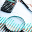 Calculator and magnifier on business graph. — Stockfoto #13780330