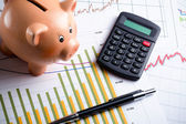 Calculator, piggy bank and pen on business graph — Stock Photo