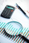 Rekenmachine en vergrootglas op zakelijke grafiek. — Stockfoto