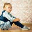 Beautiful little girl sitting on floor — Stock Photo